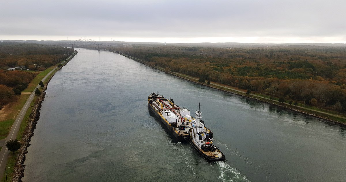tug pushing a barge through the Cape Cod Canal